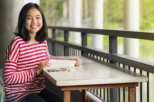 aluna asiática sentada e sorrindo lendo um livro na escola foto