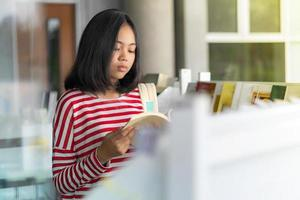 menina asiática em pé lendo um livro em livrarias foto