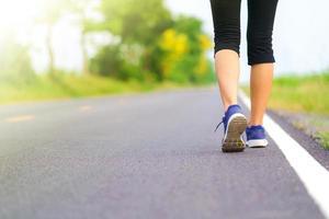 pernas de mulher andando no parque, corredor feminino correndo na estrada lá fora foto
