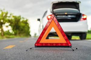 carro com problemas e um sinal de alerta com um triângulo vermelho na estrada foto