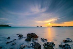 foto de longa exposição do pôr do sol sobre o mar com nuvens passando