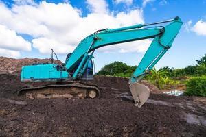 escavadeira em canteiro de obras sob céu azul foto