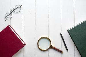 conceito de educação, livro, caneta, óculos, lupa em fundo branco de madeira foto