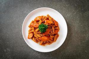 macarrão espiral ou espiral com molho de tomate e salsicha - comida italiana foto