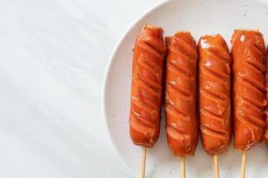 espeto de linguiça frita em prato branco foto