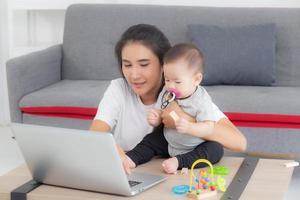 jovem mãe asiática trabalhando no computador portátil enquanto cuida da filha da filha em casa, mãe e menina sentada usando a videochamada do notebook, pais e vínculo, dentro de casa, família e conceito de negócio. foto