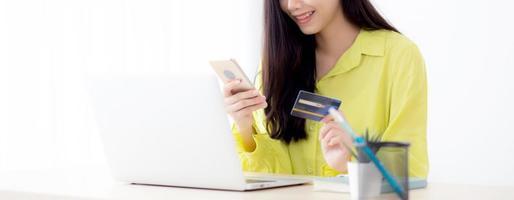 jovem mulher de negócios asiáticos usando telefone inteligente e segurando o cartão de crédito durante as compras online e pagamento online com o computador laptop na mesa em casa, mulher segurando o cartão de débito, conceito de comunicação. foto
