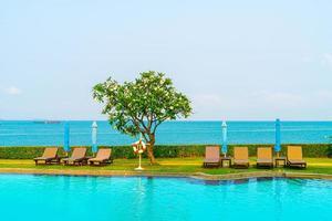 cadeira de piscina ao redor da piscina com fundo do mar - feriados e conceito de férias foto