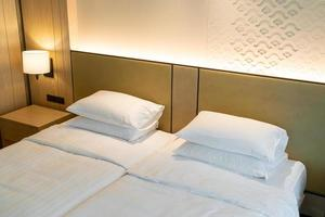 decoração de travesseiro branco na cama no quarto do hotel resort foto