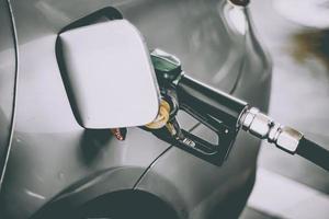 reabastecimento do bico de gasolina do carro abastecer com gasolina em um posto de gasolina. conceito de transporte e propriedade. encher o carro no conceito de posto de gasolina. foto