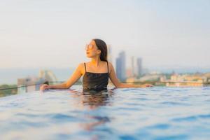 retrato lindas jovens mulheres asiáticas sorriso feliz relaxe piscina ao ar livre no hotel foto