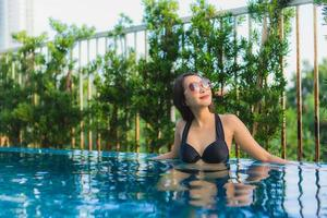 retrato lindas jovens mulheres asiáticas sorriso feliz relaxe piscina ao ar livre no resort foto