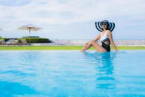 retrato lindas jovens mulheres asiáticas sorrindo feliz relaxando na piscina foto