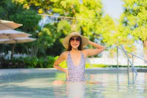 lindas jovens mulheres asiáticas sorriso feliz relaxando ao redor da piscina ao ar livre em hotel resort para viagens de férias foto
