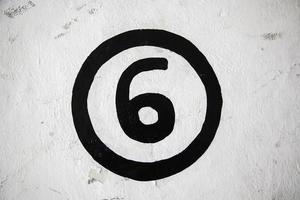número seis em uma parede branca foto