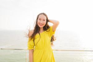 retrato bela jovem asiática sorrir feliz e relaxar na varanda ao ar livre com vista para o mar, praia e oceano foto