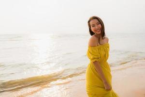 retrato linda jovem asiática caminhar na praia e no mar com um sorriso feliz relaxe foto