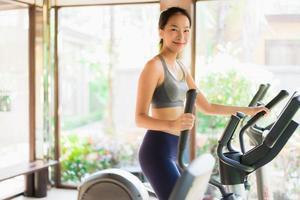 retrato bela jovem asiática exercício com equipamentos de fitness no interior do ginásio foto