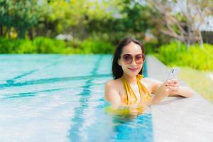 retrato bela jovem asiática usando telefone celular ou celular na piscina foto