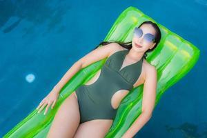 retrato bela jovem asiática sorrir feliz relaxe e lazer na piscina foto