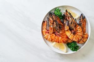 camarões tigre grelhados ou camarões com limão em um prato foto