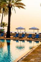 bela palmeira com piscina com cadeira de guarda-chuva em hotel resort de luxo na hora do nascer do sol - conceito de férias e férias foto