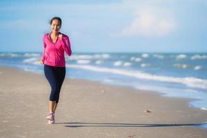 retrato bela jovem asiática correndo e se exercitando na natureza tropical ao ar livre, praia, mar, oceano foto