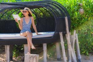 retrato bela jovem asiática lendo livro com um sorriso feliz relaxando na espreguiçadeira na praia, mar, oceano, lazer foto