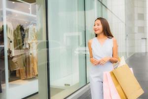 retrato linda jovem asiática feliz e sorrindo com a sacola de compras da loja de departamentos foto