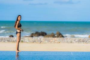 retrato bela jovem asiática usar biquíni ao redor da piscina em hotel resort perto do mar oceano praia foto