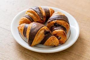croissant fresco com chocolate no prato foto