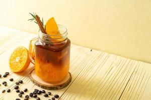 um copo de café preto americano gelado e uma camada de suco de laranja e limão decorado com alecrim e canela em um fundo de madeira foto