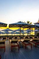 guarda-sóis e cadeiras ao redor da piscina externa em hotel resort para histórico de viagens de férias foto