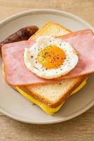 pão caseiro queijo torrado com presunto coberto e ovo frito com linguiça de porco no café da manhã foto