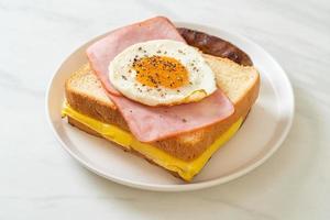 pão caseiro queijo torrado, presunto com cobertura e ovo frito com linguiça de porco no café da manhã foto