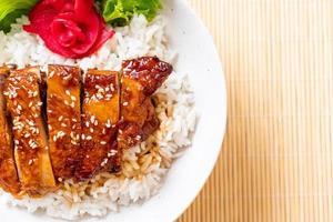 Frango grelhado com molho teriyaki na tigela de arroz com cobertura foto