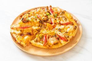 frutos do mar de camarão, polvo, mexilhão e pizza de caranguejo em bandeja de madeira foto