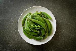 ervilhas frescas no prato branco foto