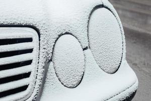 faróis de carros congelados e cobertos de gelo - condensação e gelo na superfície do carro foto