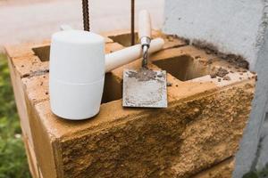 macete e pedreiro de espátula em um canteiro de obras - colocação de tijolos e telhas durante a construção e reparo foto