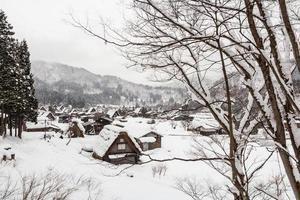 vila de Shirakawago com queda de neve no inverno foto
