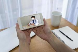 paciente mulher que teve febre e tosse com suspeita de infecção por covid-19 ou coronavírus, consulte um médico asiático por telefone. telemedicina e novo conceito de estilo de vida normal foto