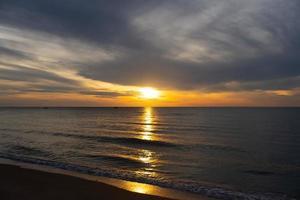 lindo pôr do sol na praia no verão com reflexo do sol na água foto