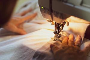 feche as mãos da mulher sênior usando a máquina de costura para costurar roupas em casa foto