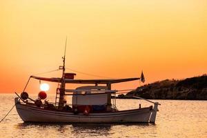 paisagem com barco de pesca no mar com lindo nascer do sol no fundo foto