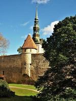 torre do sino da igreja de São Nicolau em Tallinn, Estônia, vista atrás de uma torre na muralha da cidade foto