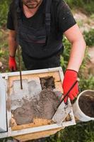 adesivo à base de cimento para bloco de pedra de alvenaria e tijolo em construção - um pedreiro profissional no trabalho foto