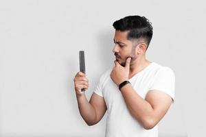 retrato de close-up de aparência perfeita incrível jovem segurando um pente na mão isolado sobre fundo branco foto