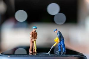 trabalhadores em miniatura com ferramentas para consertar telefones celulares foto