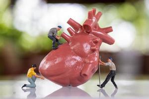 equipe de trabalho de pessoas em miniatura examina o coração, ouve os batimentos cardíacos e faz um diagnóstico foto